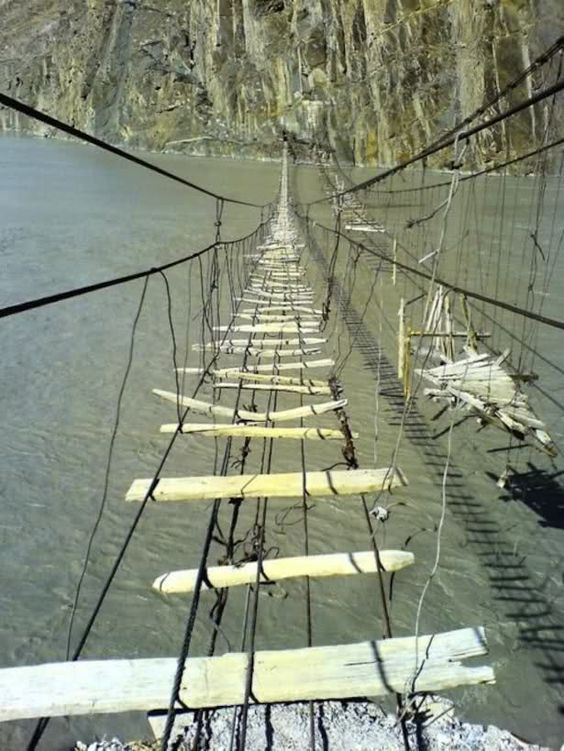 Image of a very precarious-looking rope bridge with intermittent slats of wood and branches. It stretches across a wide river to a sheer muddy bank the other side.